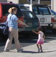Parent and child walking to car from San  Mateo Gymnastics on Karen Road, Belmont, CA